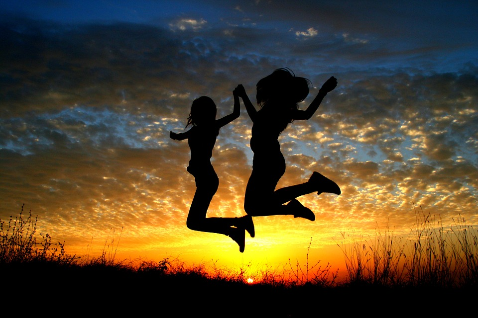 two females jumping holding hands infront of sunset